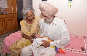 Indian parents Mohinder Singh Gill (R), 79, and Daljinder Kaur, 70, hold their newborn baby boy Arman at their home in Amritsar on May 11, 2016. An Indian woman who gave birth at the age of 70 said May 10 she was not too old to become a first-time mother, adding that her life was now complete. Daljinder Kaur gave birth last month to a boy following two years of IVF treatment at a fertility clinic in the northern state of Haryana with her 79-year-old husband. / AFP PHOTO / NARINDER NANU