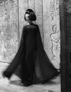 An Italian model with 'Cleopatra' hairstyle wearing a black chiffon fitting dress. Italy, 1962