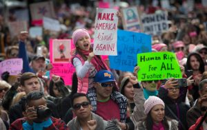 Maya Farias, 7, of San Jose, with her father, Eddie Farias, cheers during the Women's March rally at Plaza de Cesar Chavez Park in downtown San Jose, Calif., Saturday, Jan. 21, 2017. (Patrick Tehan/Bay Area News Group)
