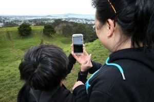 AUCKLAND, NEW ZEALAND - JULY 13: Elaine Chung (R) says Pokemon Go is a great way to bond with her son Samuel (L) as they search on the summit of Mount Eden on July 13, 2016 in Auckland, New Zealand. The augmented reality app requires players to look for Pokemon in their immediate surroundings with the use of GPS and internet services turning the whole world into a Pokemon region map. The hugely popular app has seen Nintendo shares soar following its limited release in the U.S., Australia and New Zealand on July 6. (Photo by Fiona Goodall/Getty Images)