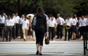 Bloomberg Photo Service 'Best of the Week': A woman waits to cross a road in the Kasumigaseki area of Tokyo, Japan, on Thursday, Sept. 11, 2014. Losing women from the workforce in their 20s and 30s to look after children is no longer an option for Japan as its aging workforce means there will be fewer and fewer men to fill the positions. Photographer: Tomohiro Ohsumi/Bloomberg