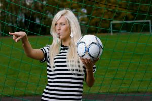 blonde_woman_with_black_and_white_stripped_clothing_with_a_football_ball_and_a_whistle